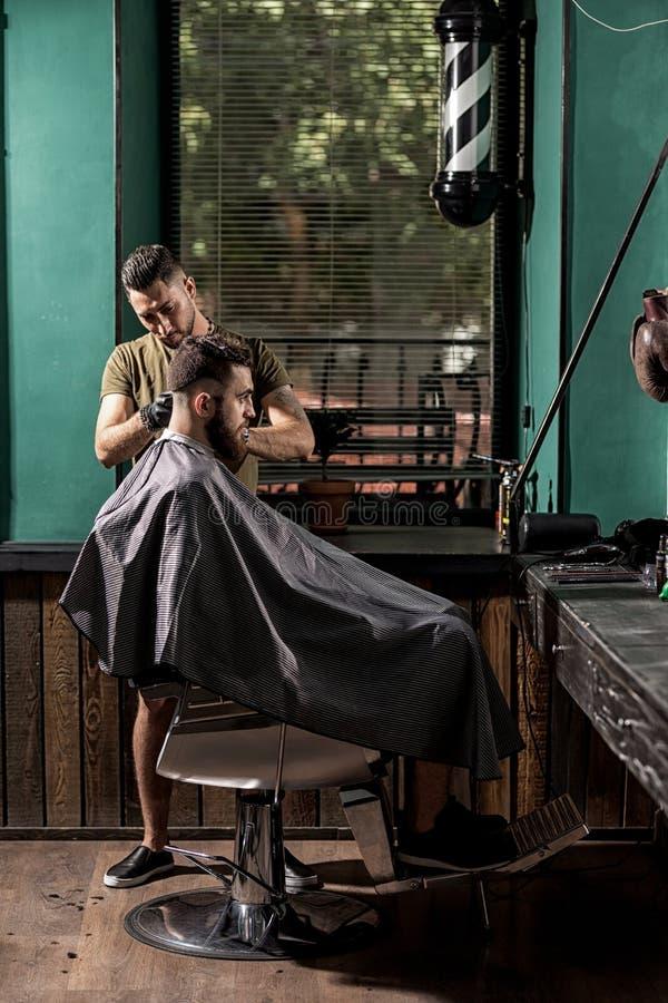 O homem brutal com barba senta-se em uma barbearia O barbeiro considerável faz uma guarnição do cabelo fotos de stock