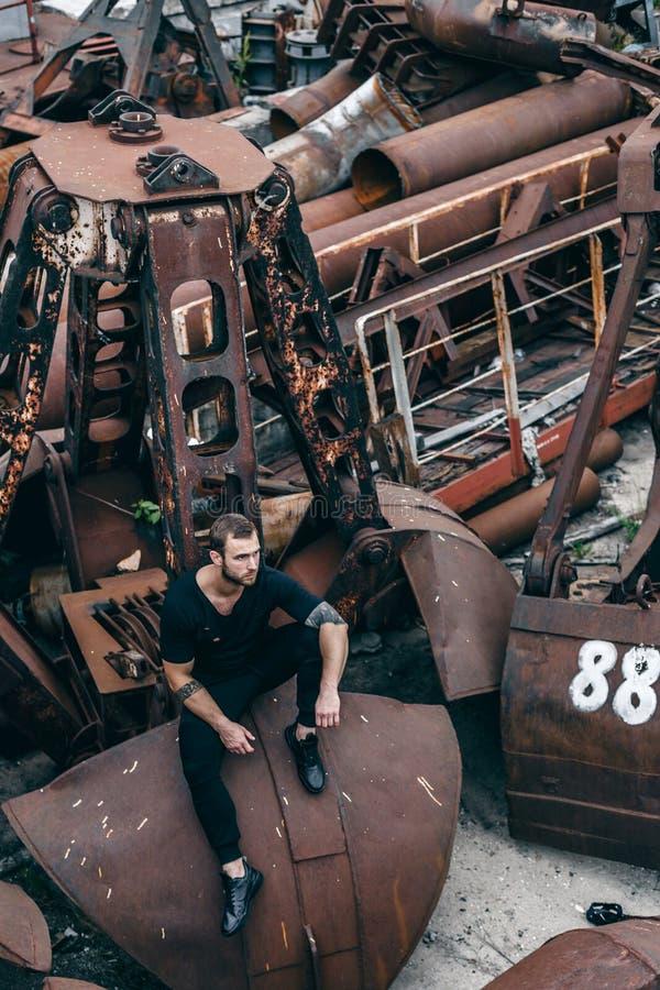 O homem brutal com uma barba senta-se em uma concha oxidada do metal de uma fábrica abandonada fotos de stock royalty free