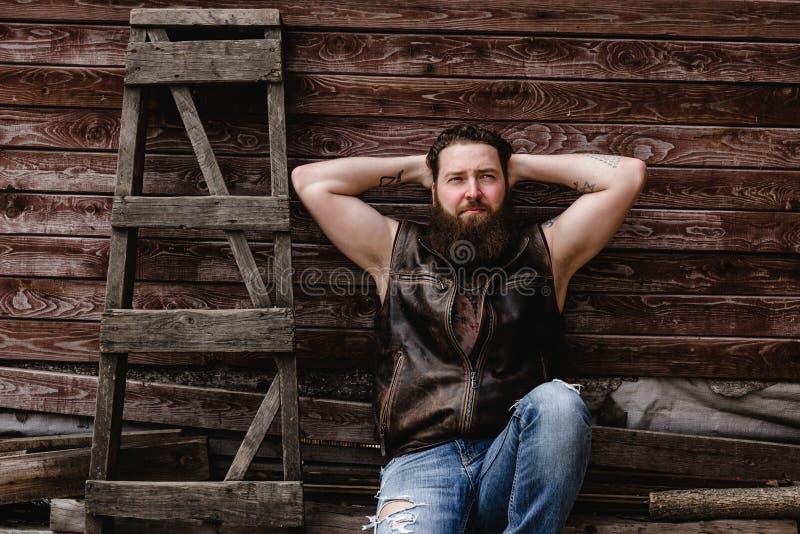 O homem brutal forte com uma barba e tatuagens em suas m?os vestidas na veste e nas cal?as de brim de couro senta-se em uma pared fotos de stock