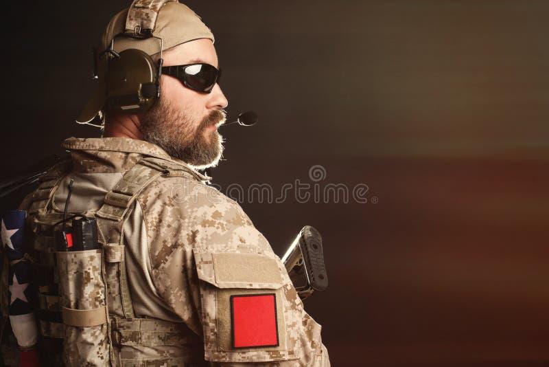 O homem brutal no uniforme e na armadura militares do deserto é patético e examina afastado o fundo preto no estúdio O bea foto de stock