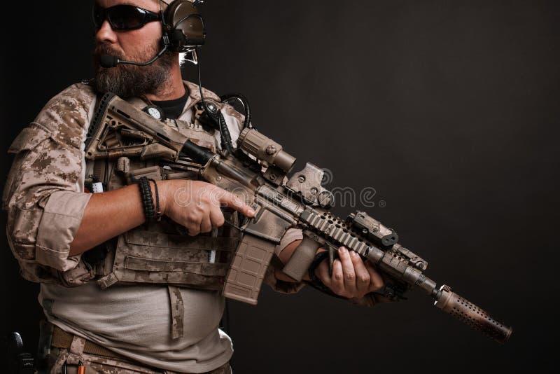 O homem brutal no uniforme e na armadura militares do deserto está em uma cremalheira de combate e guarda seu rifle em um fundo p imagem de stock