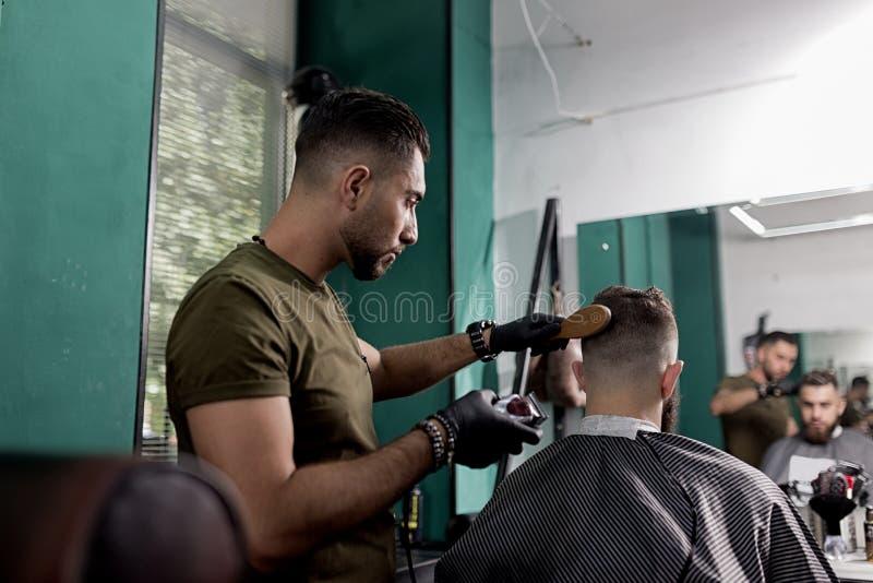 O homem brutal senta em uma barbearia na parte dianteira o espelho O barbeiro em luvas pretas barbeia os cabelos do homem foto de stock