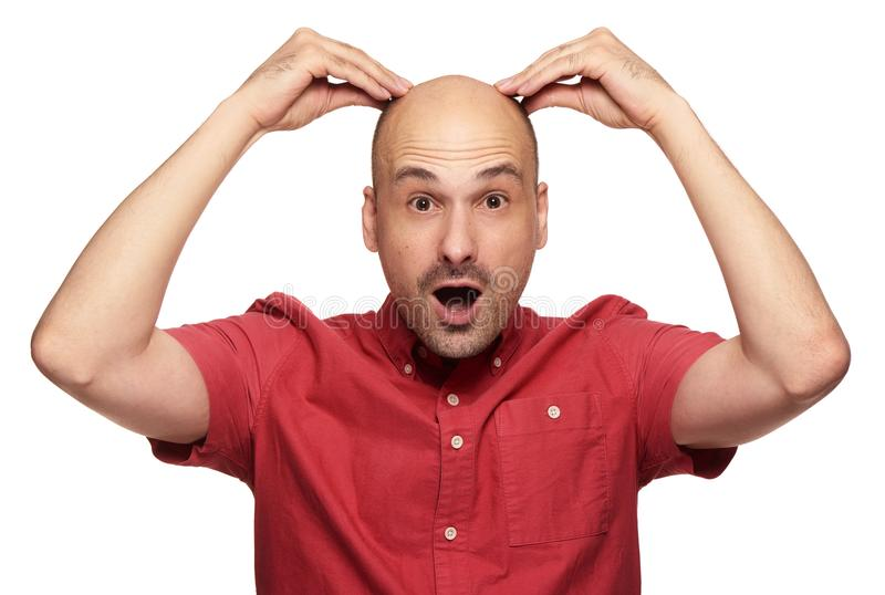 O homem calvo chocado guarda sua cabeça Isolado imagens de stock royalty free