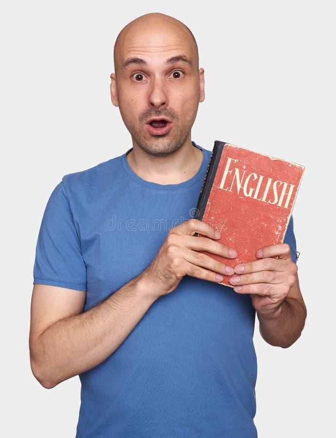 O homem calvo chocado guarda um livro de texto inglês imagens de stock royalty free