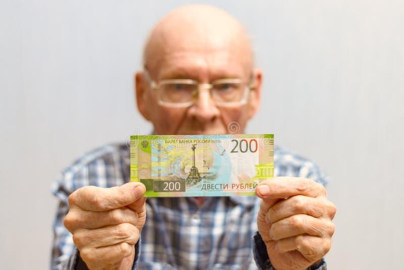 O homem calvo de Оld com vidros guarda uma cédula de 200 rublos na frente dele fotos de stock royalty free