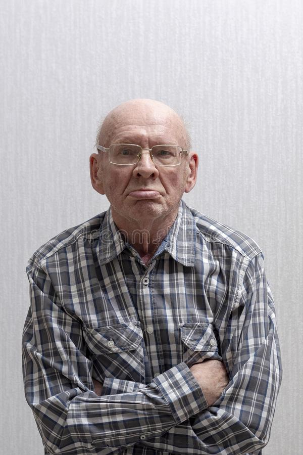 O homem calvo idoso nos vidros mostra o dedo m?dio foto de stock