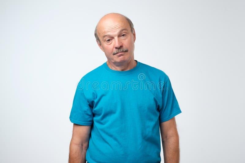 O homem cansado idoso superior está abrindo mal seus olhos imagens de stock royalty free