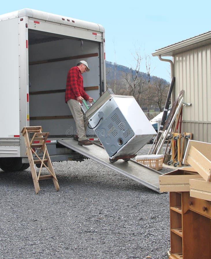 O homem carrega camionete movente foto de stock