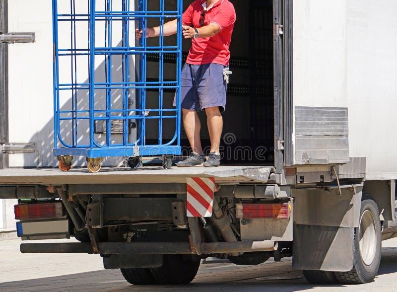 O homem carrega um caminhão ao lado de um armazém foto de stock royalty free