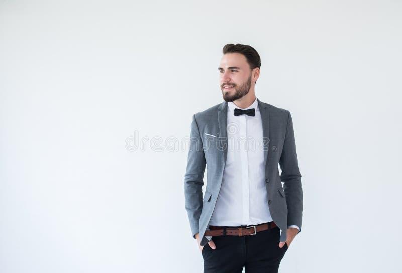 O homem caucasiano considerável com o farpado na posição formal do smoking e do terno e no sorriso no fundo branco, copia o espaç imagens de stock