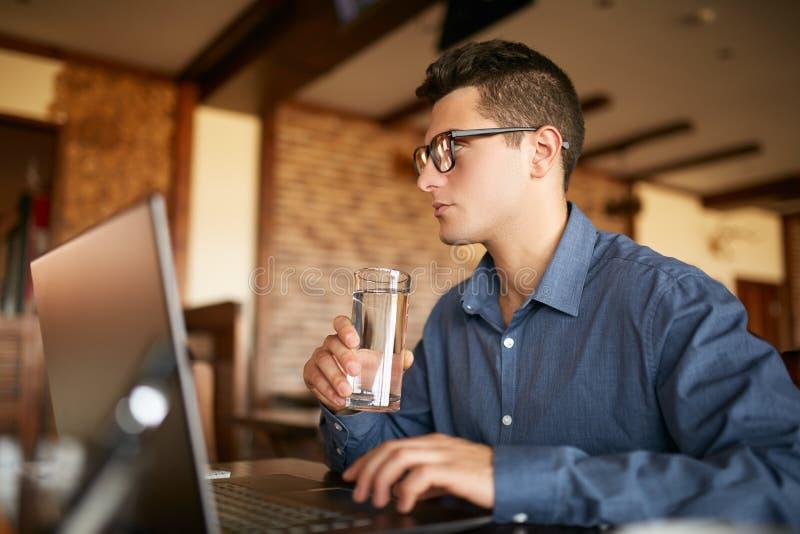 O homem caucasiano considerável com vidro da água trabalha à disposição com portátil Homem de negócios na água das bebidas dos vi foto de stock royalty free