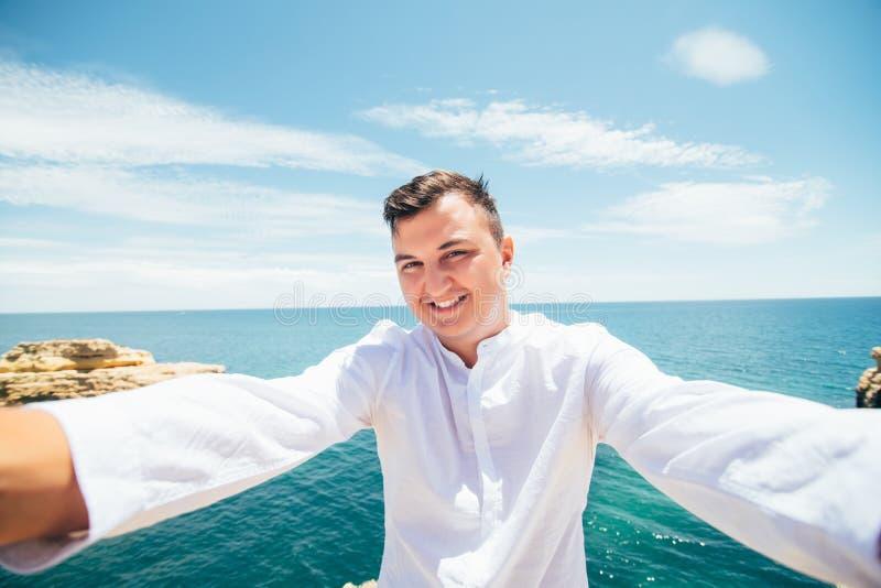 O homem caucasiano considerável na camisa branca toma um selfie no fundo do oceano da praia o Povos, estilo de vida e conceito da imagens de stock royalty free