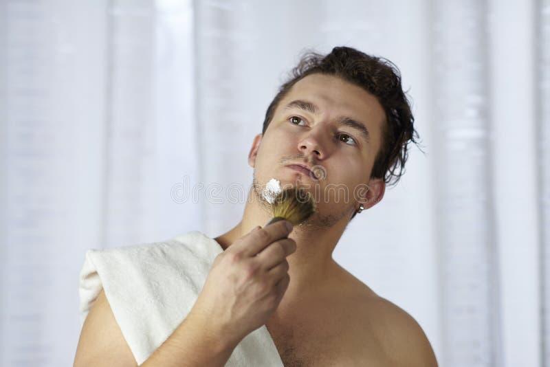 O homem caucasiano considerável novo começa a barbear com escova e espuma, estilo do vintage do barbeiro idoso Olhar sério pensat imagens de stock royalty free