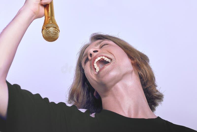 O homem caucasiano considerável novo que canta no microfone dourado, boca espalhou extensamente, emoções e expressão fortes conce foto de stock royalty free
