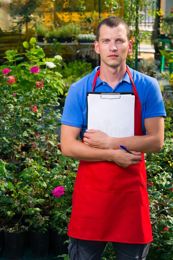 O homem caucasiano está tomando notas em uma estufa da flor foto de stock