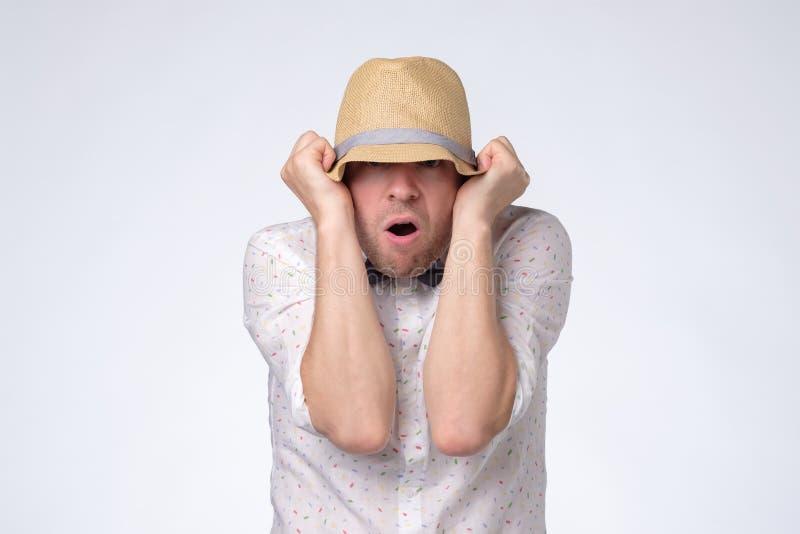O homem caucasiano novo fecha a cara com o chapéu que tenta ficar o anônimo imagem de stock