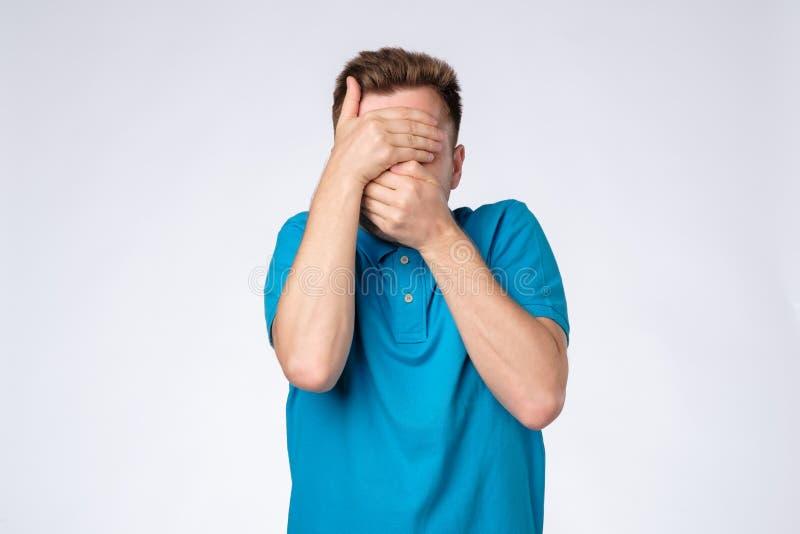 O homem caucasiano novo na camisa azul fecha a cara com as mãos que tentam ficar o anônimo fotos de stock royalty free