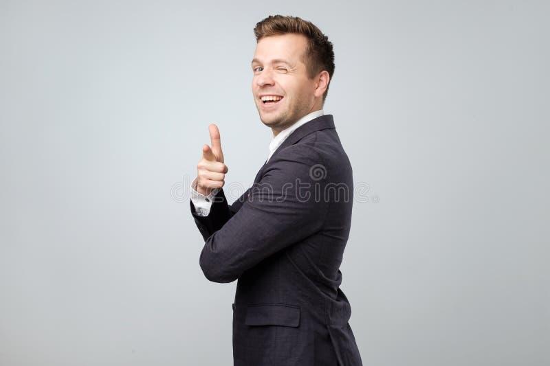 O homem caucasiano novo no terno que aponta na câmera como dizê-lo é gajo adequado fotos de stock royalty free
