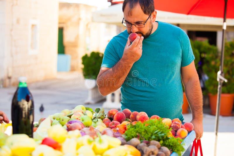 O homem cheirando pêssego no mercado ao ar livre imagem de stock