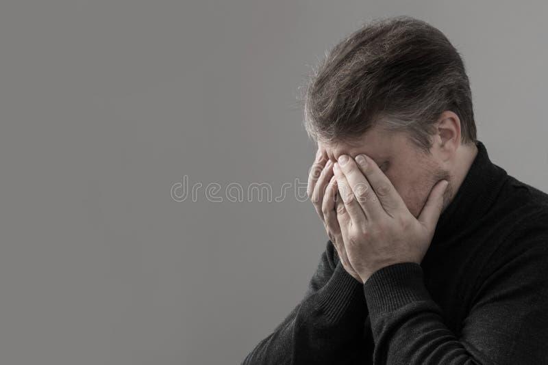 O homem cobriu sua cara com suas m?os fotografia de stock
