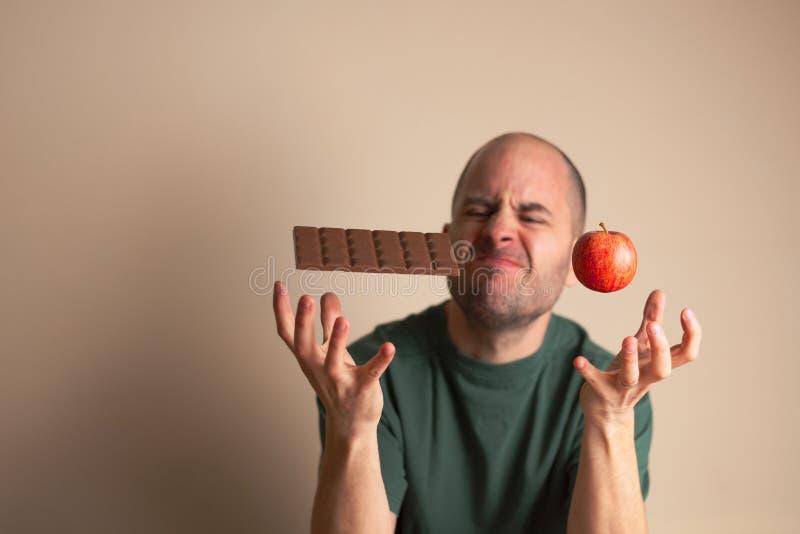 O homem coloca uma mão debaixo de uma barra de chocolate e a outro debaixo de uma maçã fotos de stock royalty free