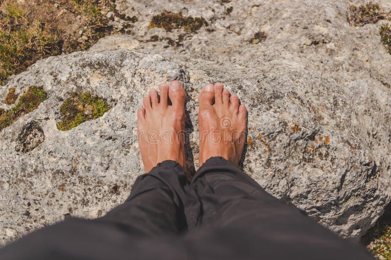 O homem colocou com os pés descalços em uma rocha fotos de stock royalty free