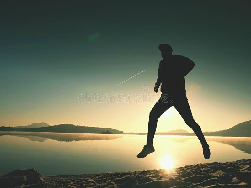 O homem com óculos de sol, o boné de beisebol vermelho e o sportswear preto vermelho é de corrida e de exercício na praia imagens de stock royalty free