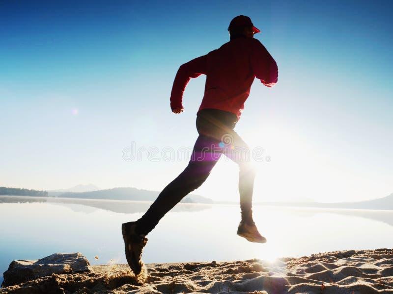 O homem com óculos de sol, o boné de beisebol vermelho e o sportswear preto vermelho é de corrida e de exercício na praia fotos de stock royalty free