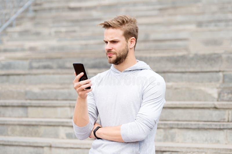 O homem com barba anda com smartphone, fundo urbano com escadas Smartphone do uso do Blogger para fluir em linha o vídeo Homem fotografia de stock royalty free