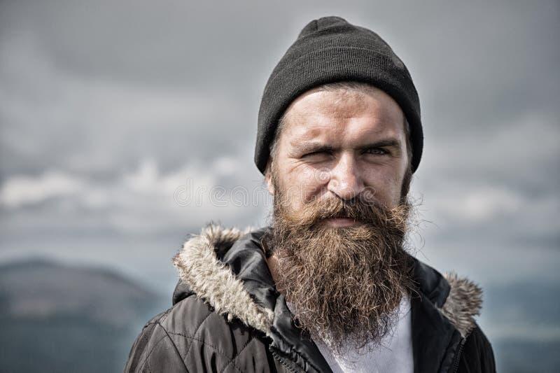 O homem com barba e o bigode longos veste o chapéu O moderno na cara restrita com barba olha brutalmente ao caminhar masculinity imagem de stock royalty free
