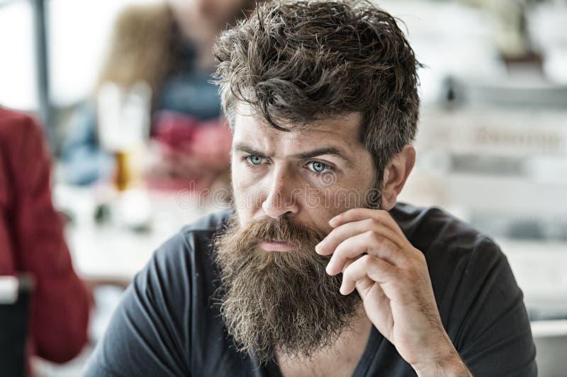 O homem com barba e bigode senta exterior no terraço do café O homem farpado na cara calma olha triste e incomodado Moderno com foto de stock royalty free