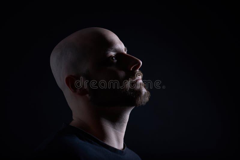 O homem com a barba em escuro - fundo cinzento fotos de stock