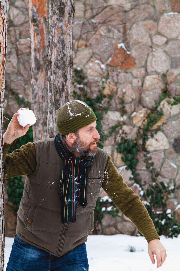 O homem com a barba em seus lances do waistcoat aumenta rapidamente entre árvores imagens de stock