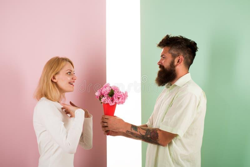 O homem com barba felicita o feriado do aniversário do aniversário da mulher O moderno farpado dá flores do ramalhete à amiga imagens de stock royalty free