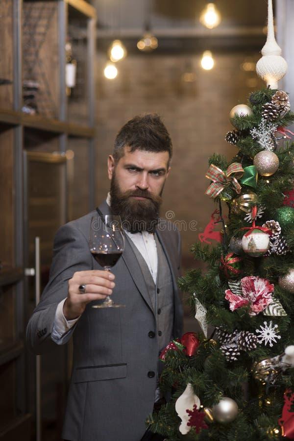 O homem com barba longa comemora o ano novo e o Natal O moderno aprecia o vinho no restaurante Bebidas do partido do Xmas, brinde foto de stock