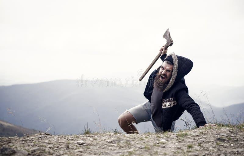 O homem com a barba na cara da gritaria conquista a parte superior da montanha com machado, fundo do c?u Sobreviva no conceito se imagem de stock royalty free