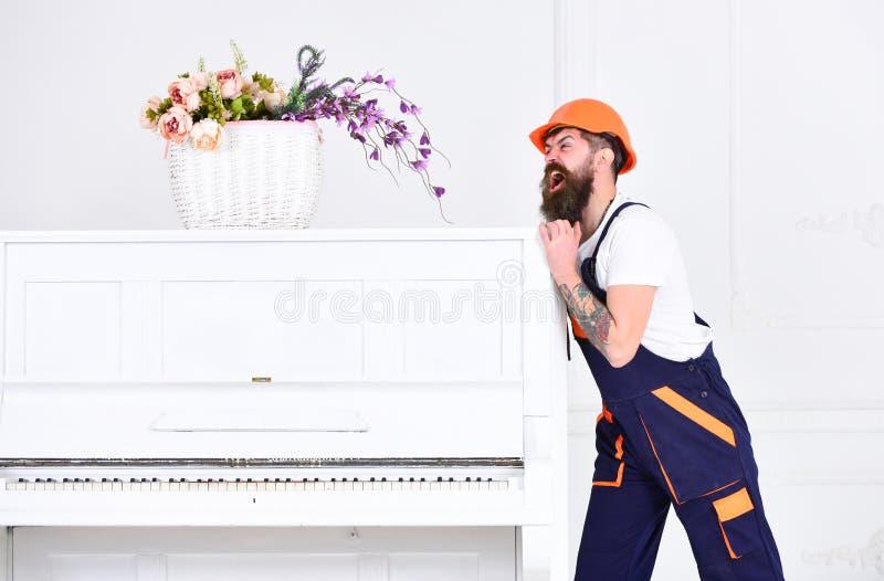 O homem com barba, trabalhador nos macacões e capacete empurra o piano, fundo branco Conceito do serviço de entrega Movimentos do fotografia de stock royalty free