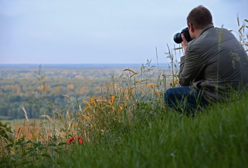 o homem com a câmera senta-se em um monte verde alto ao lado das flores vermelhas da papoila imagens de stock royalty free