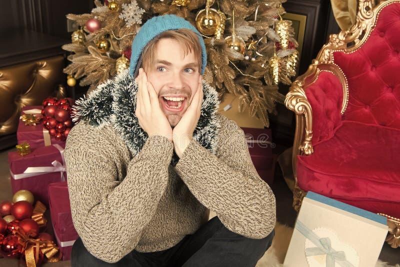 O homem com cara feliz senta-se na árvore do xmas na sala fotos de stock