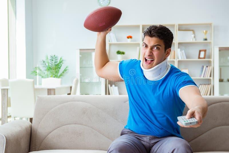 O homem com ferimento do pescoço que olha o futebol americano em casa imagens de stock