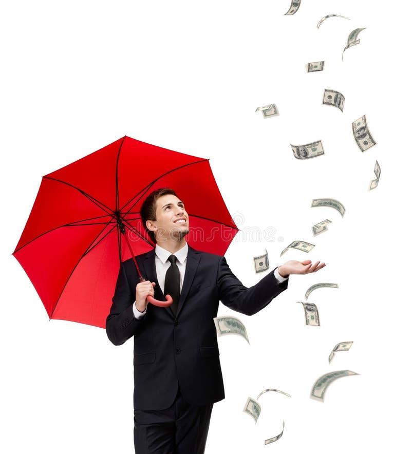 O homem com guarda-chuva vermelho olha o dinheiro de queda fotos de stock royalty free