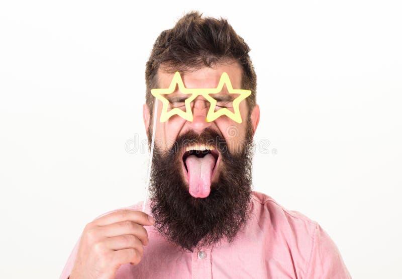 O homem com língua do stickout, os olhos fechados e a estrela de papel vestindo da barba deu forma a vidros, conceito do divertim fotografia de stock royalty free
