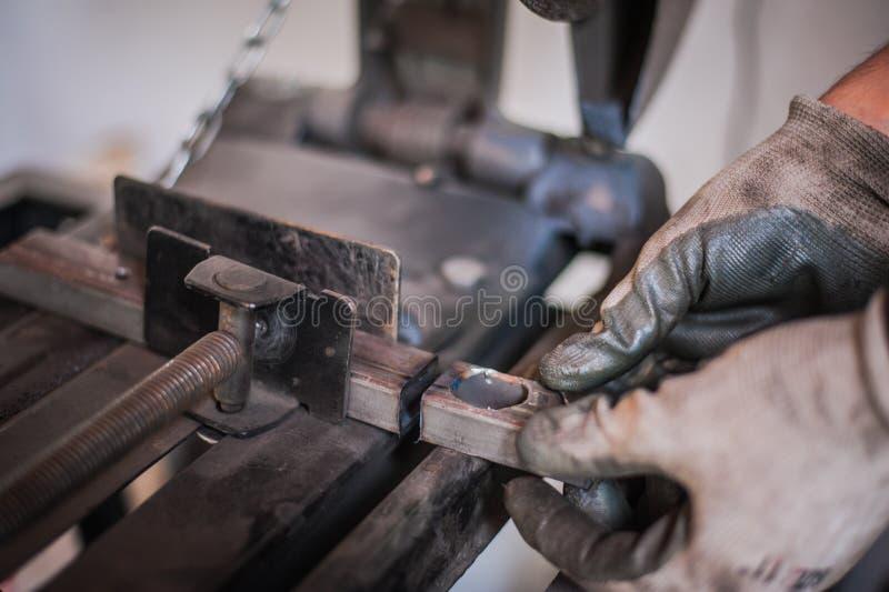 O homem com luvas protetoras guarda o metal cortado após a moedura fotografia de stock