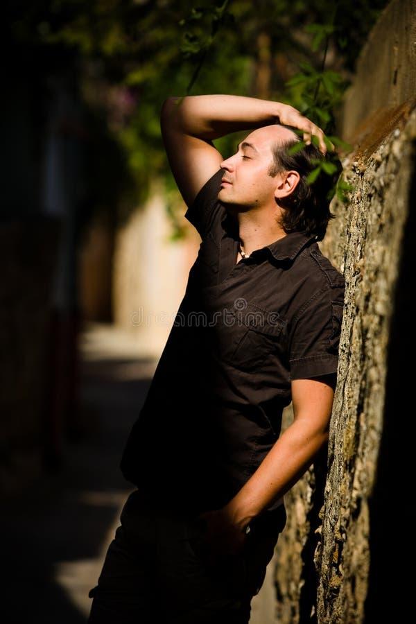 O homem com mão levantada inclina a parede na rua foto de stock royalty free