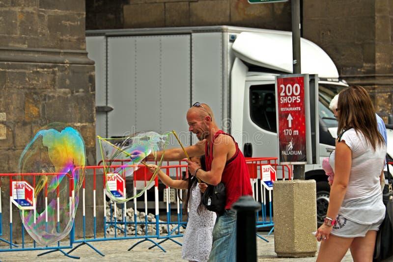 O homem com menina faz bolhas grandes fotos de stock royalty free