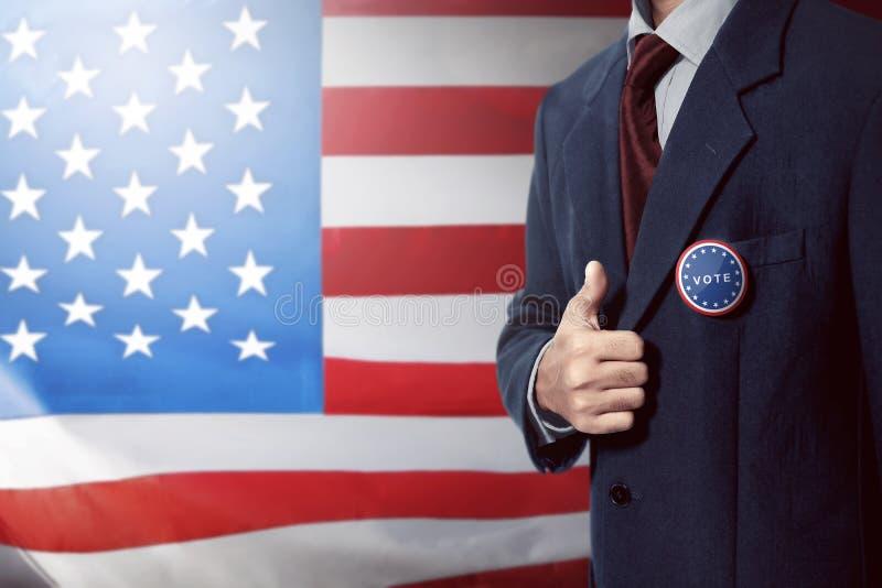 O homem com o terno de negócio preto com o botão fixado voto dá o polegar imagem de stock royalty free