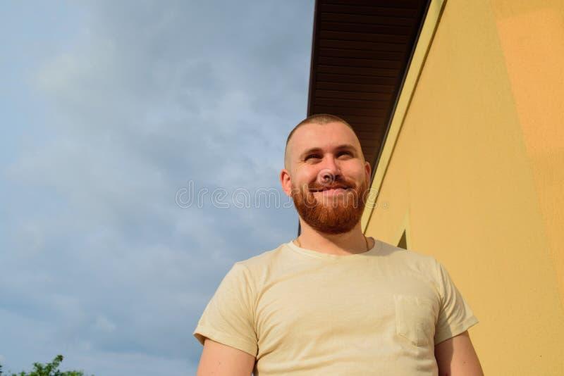 O homem com penteado na moda e barba, olha com expressão séria, tem a barba vermelha grossa O homem está sorrindo sinceramente fotos de stock royalty free