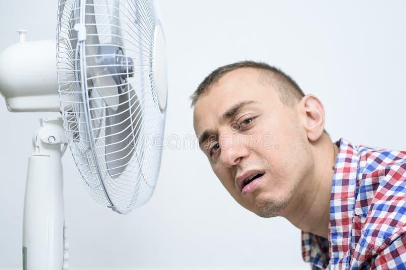 O homem com restolho em sua cara sofre do calor e da tentativa refrigerar fora perto do fã foto de stock royalty free