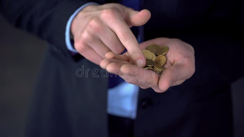O homem com o salário médio que conta moedas, baixo salário, despesas excede rendimentos fotos de stock