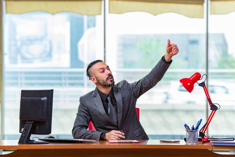 O homem com seus polegares acima na mesa de escritório fotos de stock